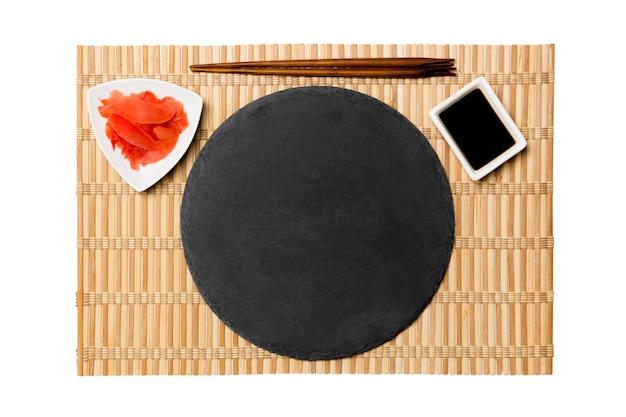 Piatto vuoto in ardesia nera con bacchette per sushi e salsa di soia, zenzero sulla superficie della stuoia di bambù giallo