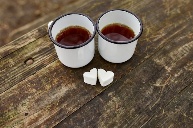 Tazze di tè smaltate in natura su una superficie di legno con marshmallow