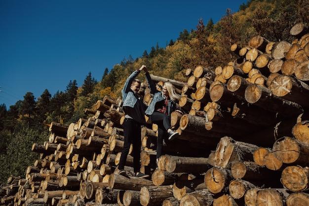 Coppia innamorata in piedi su legna da ardere nella foresta.