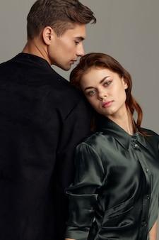 Uomo e donna innamorati stanno con le spalle l'un l'altro sfondo grigio vista frontale