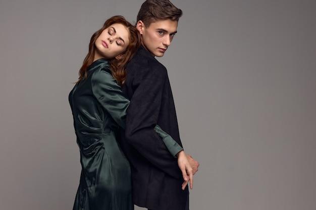 Uomini e donne innamorati stanno con le spalle l'un l'altro su un muro grigio.