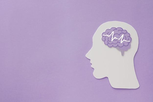 Ritaglio di carta cerebrale di encefalografia su sfondo viola, consapevolezza di epilessia e alzheimer, disturbo convulsivo, concetto di salute mentale