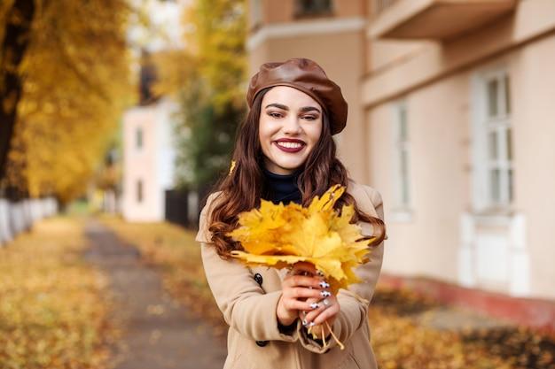 Incantevole donna caucasica sta mostrando il mazzo di foglie di acero gialle nelle sue mani