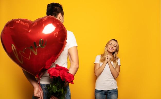 Una donna incantevole in un abito casual tiene le mani insieme con impazienza, cercando di guardare le rose e una scatola a forma di cuore, che suo marito nasconde dietro la schiena.