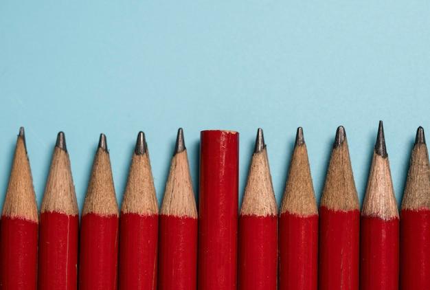 La fine di una matita rossa viene spostata sulla punta del gruppo matita rossa, il diverso pensiero e il concetto di leadership di disruption.