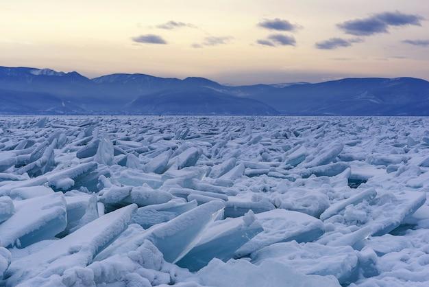 Campo infinito di collinette sul lago ghiacciato baikal. mucchi di detriti innevati di ghiaccio blu in una gelida giornata. sfondo naturale freddo. insolito paesaggio invernale