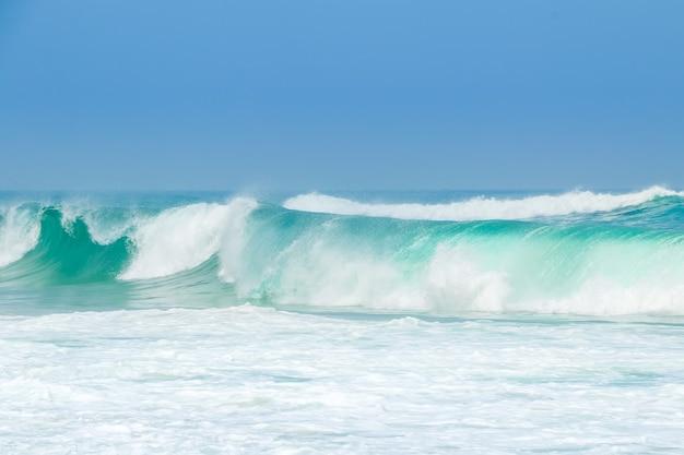 Oceano infinito. una grande onda verde di surf e molta schiuma in primo piano