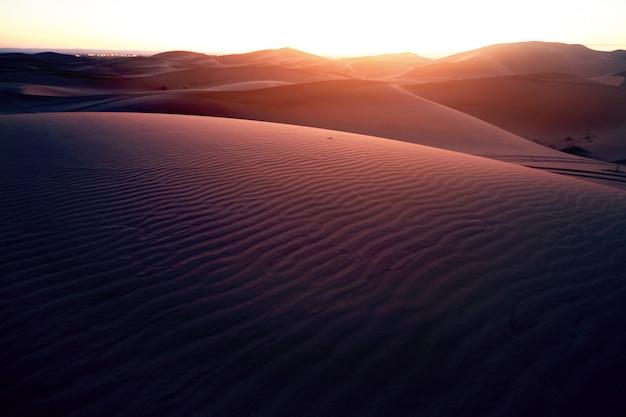 Infinite sabbie del deserto del sahara, il caldo sole cocente splende sulle dune di sabbia. marocco merzouga