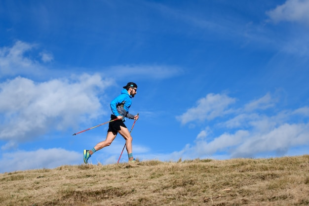 Gara di resistenza in montagna. un uomo con pali da arrampicata