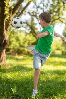 Ragazzo energico che dà dei calci al pallone da calcio indietro.