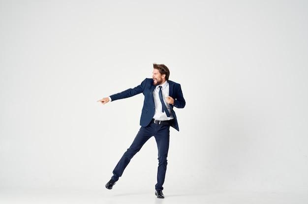L'uomo energico di affari in un vestito blu salta in su