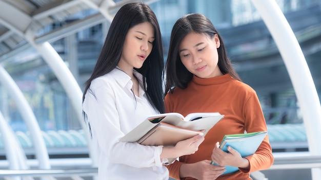 Ragazze adolescenti ottimiste energiche con fermo e libro e leggere.