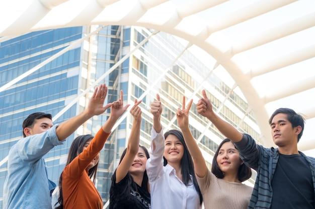Gli adolescenti energici e ottimisti mostrano la mano con molti simboli di tonfo