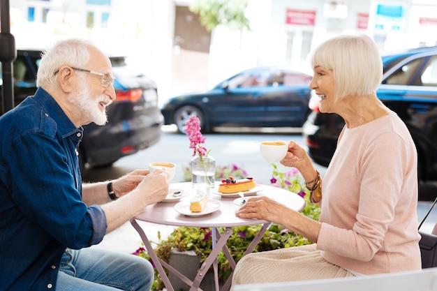 Energica coppia senior seduti al bar e bere caffè