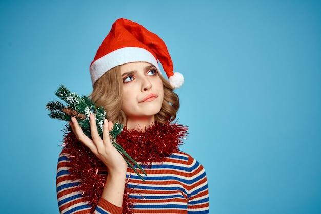 Donna energica con albero di natale mani rami di albero modello cappello rosso nuovo anno