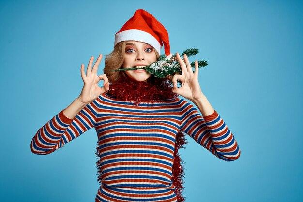 Donna energica con albero di natale mani rami di albero modello cappello rosso