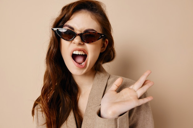 Donna energica con occhiali e cappotto beige acconciatura bocca spalancata