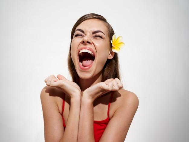 Una donna energica con la bocca aperta grida su uno sfondo chiaro e tiene le mani vicino al viso