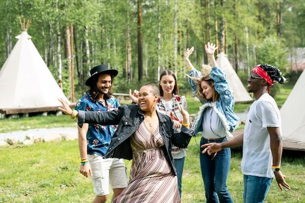 Energici giovani multietnici che ballano al festival musicale situato nella foresta
