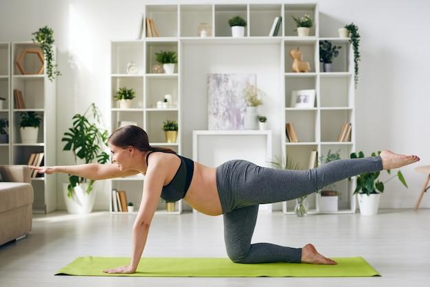 Energica giovane donna incinta in abiti sportivi praticando il bilanciamento della tabella pongono sul materassino yoga in soggiorno