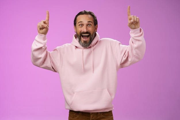 Eccitato felice di bell'aspetto alla moda papà maturo barba capelli grigi in rosa felpa con cappuccio elegante che indossa il vestito da figlio rivolto verso l'alto le dita degli indici entusiasti gruppo musicale preferito in città, in piedi sfondo viola.