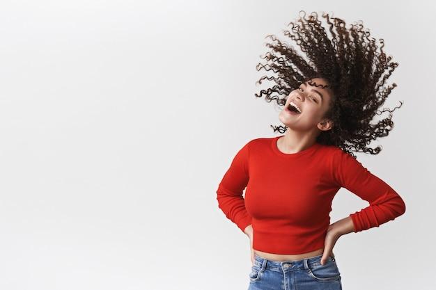 Eccitato vivace felice bella gioiosa ragazza riccia scura acconciatura agitando scuotendo la testa riccioli volare aria ridere allegro ballare divertirsi esibendo taglio di capelli perfetto in piedi muro bianco