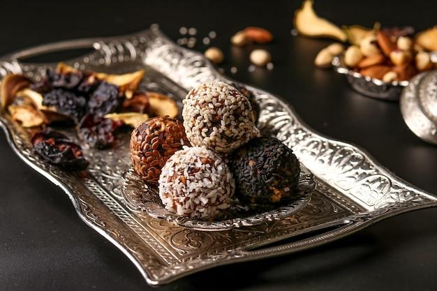 Palline energetiche di noci, farina d'avena e frutta secca su un vassoio di metallo su uno sfondo scuro