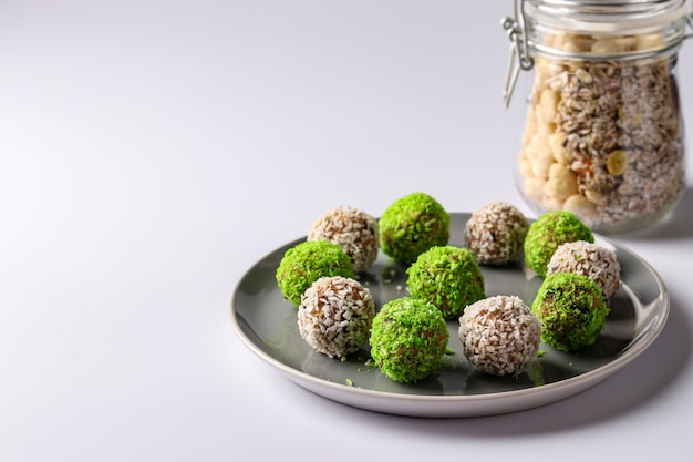 Palline energetiche di noci, farina d'avena e frutta secca, cosparse di scaglie di cocco verde e bianco su un piatto