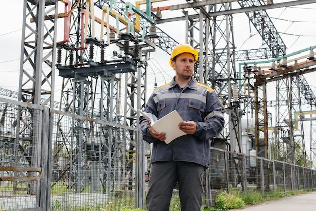 L'ingegnere energetico ispeziona le apparecchiature della sottostazione. ingegneria energetica. industria.