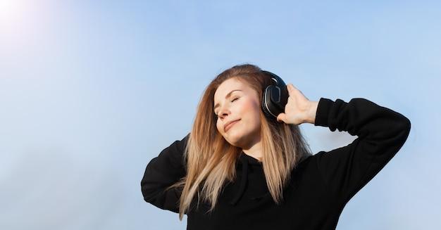 Ragazza di energia con le cuffie blu che ascolta la musica con gli occhi chiusi sulla parete blu. indossa una felpa con cappuccio nera. i lunghi capelli ricci nella coda volano dal movimento.