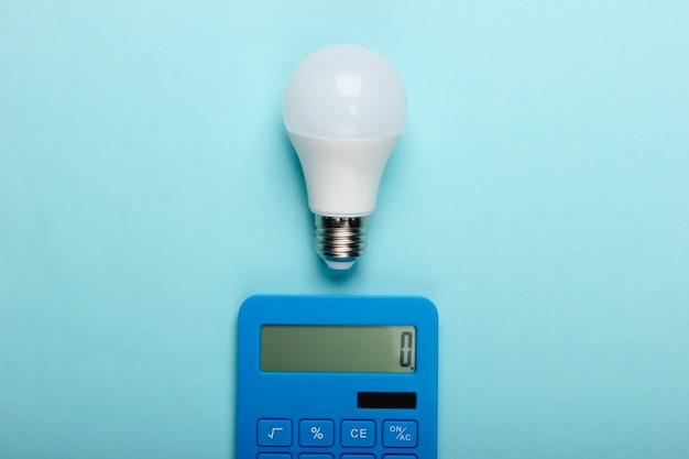 Risparmio energetico. calcolatrice con lampadina a led su sfondo blu pastello. vista dall'alto