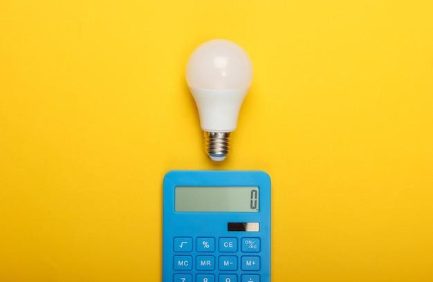 Risparmio energetico. calcolatrice con lampadina a led su sfondo giallo. vista dall'alto