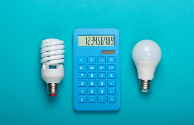 Risparmio energetico. calcolatrice con led e lampadina a spirale su sfondo blu. vista dall'alto