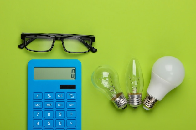 Risparmio energetico. calcolatrice con lampadine, bicchieri sul verde