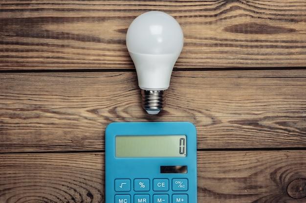 Concetto di risparmio energetico. calcolatrice con lampadina su un legno