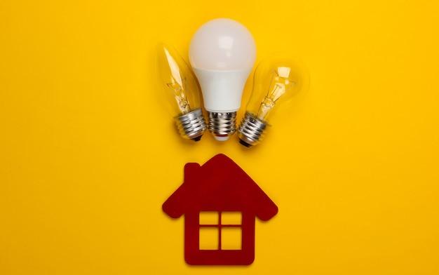 Concetto di risparmio energetico. statuetta di casa e lampadine su giallo
