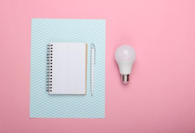 Concetto di risparmio energetico. blocco note con lampadina a led su sfondo blu rosa. ho un'idea!
