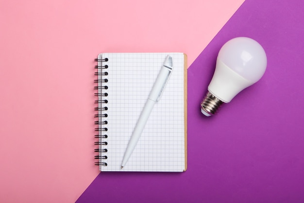 Concetto di risparmio energetico. blocco note con lampadina a led su sfondo rosa viola. ho un'idea!