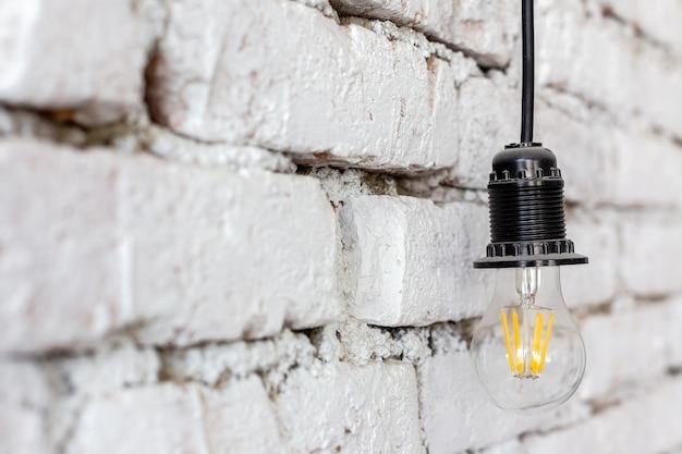 Lampada a led a risparmio energetico appesa a un muro bianco grezzo in un design di lusso di una moderna camera d'albergo loft.