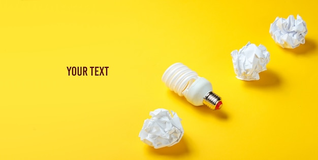 Lampadina a risparmio energetico e palline di carta stropicciata su sfondo giallo. concetto di business minimalista, idea. copia spazio