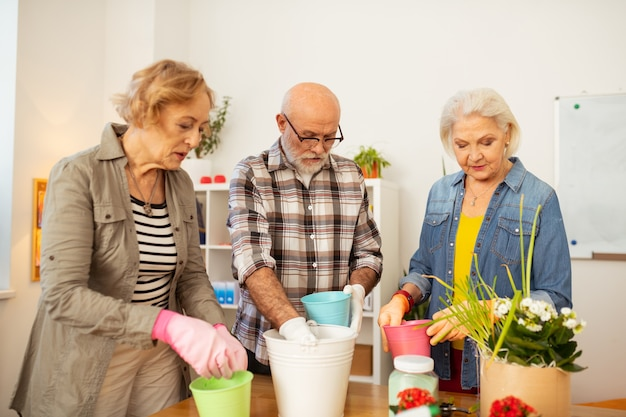 Impegnato nel giardinaggio. persone anziane serie che guardano nei vasi di fiori mentre sono impegnate nel giardinaggio