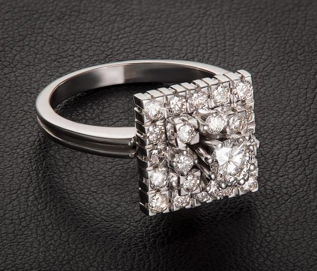 Anello di fidanzamento con diamante su pelle nera. lusso