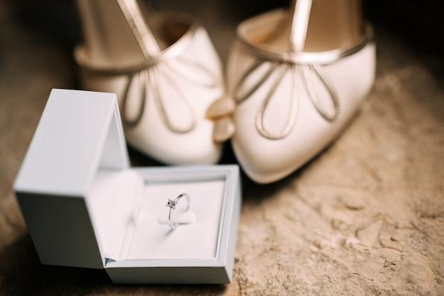 Un anello di fidanzamento in una scatola bianca aperta sul pavimento con scarpe da sposa da donna con treccia