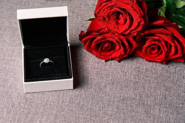 Anello di fidanzamento e rose rosse come regalo. concetto di san valentino e matrimonio.