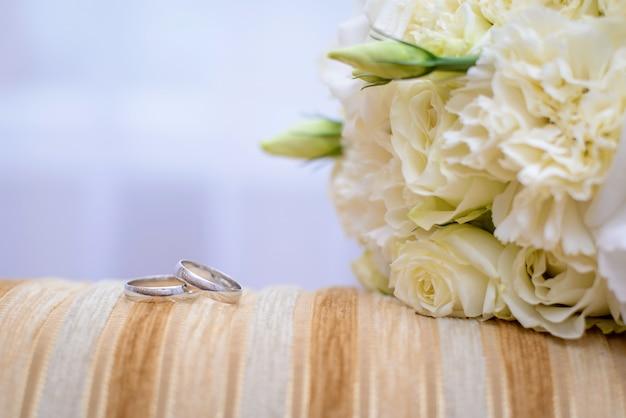 Anelli di fidanzamento e bouquet da sposa
