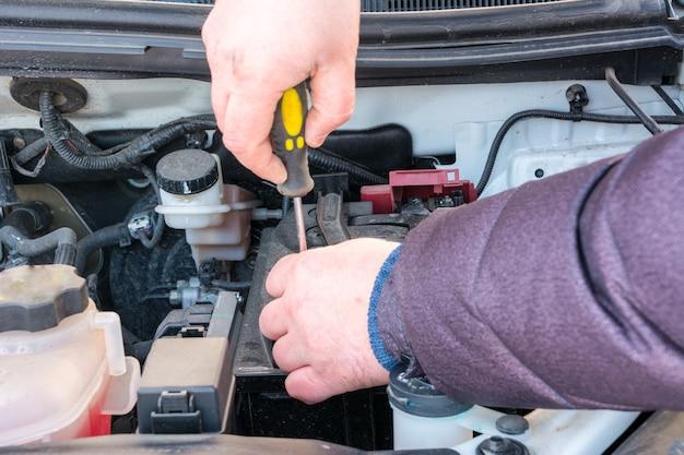 Il tecnico del motore sta sostituendo la batteria dell'auto perché la batteria dell'auto è scarica. manutenzione di concept car in inverno.