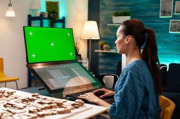 Architetto ingegnere che utilizza lo schermo verde e il progetto