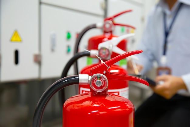 Ingegnere ispezione estintore nella sala controllo incendi.