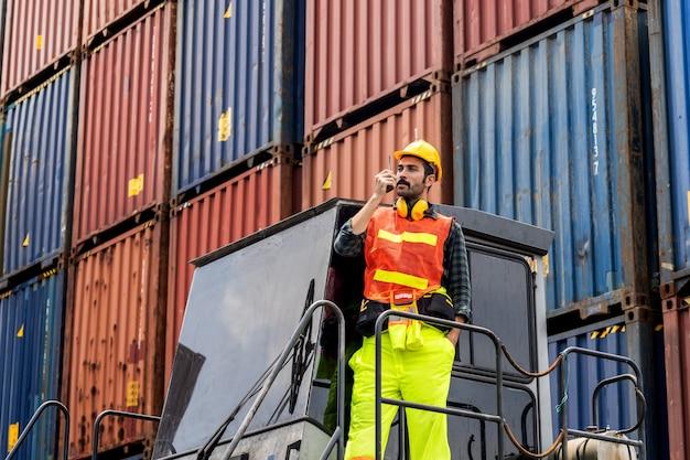 Uomo di barba ingegnere in piedi con articoli un casco giallo per controllare il carico e controllare la qualità dei container dalla nave da carico per l'importazione e l'esportazione al cantiere navale o al porto