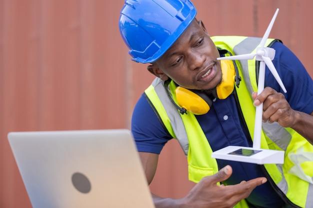 Ingegnere lavoratore nero che discute di energia solare dal modello di turbina eolica e online